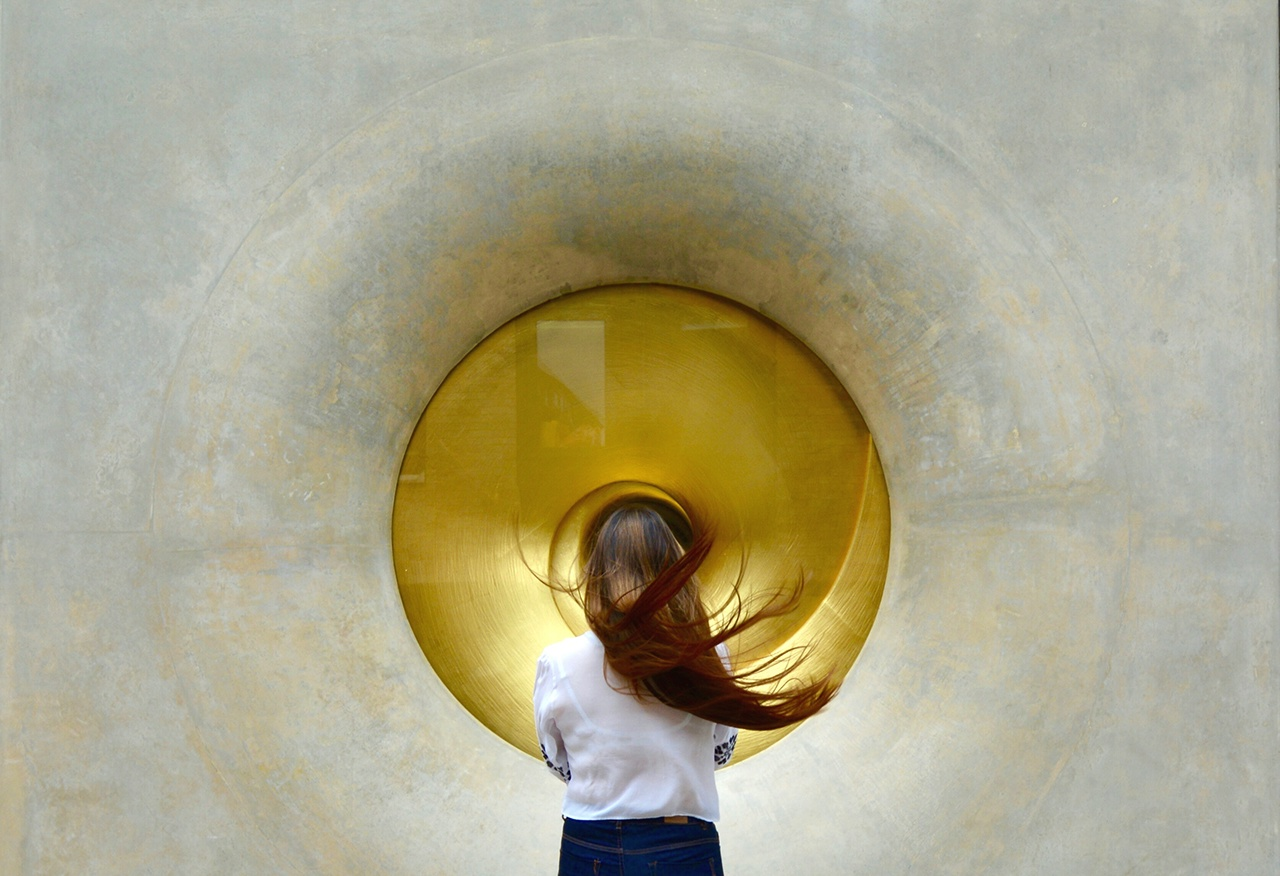 Rear View Of Woman Looking At Gold Circle On Wall