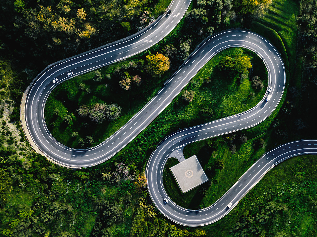 Aerial view of winding curved road with helicopter parking in Italy countryside
