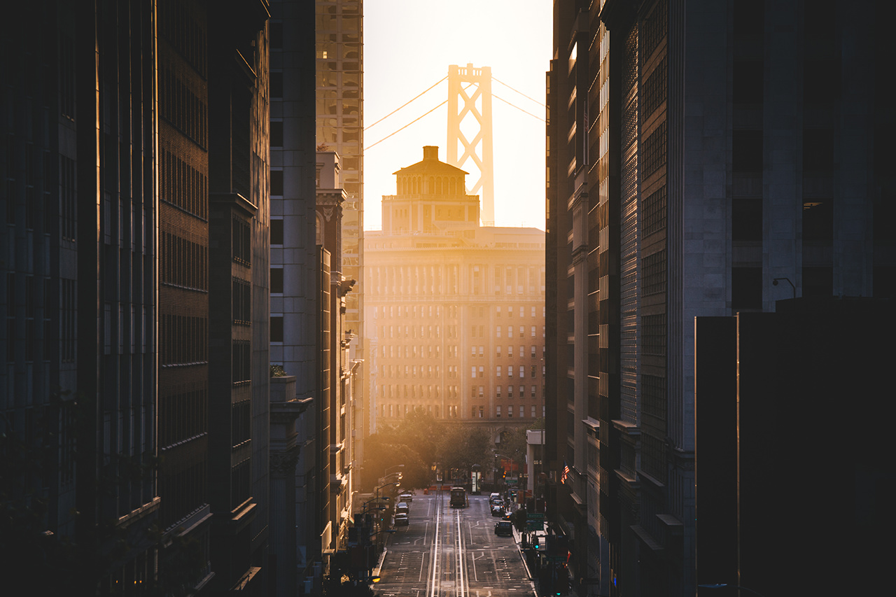 Downtown San Francisco with famous California Street illuminated in first golden morning light at sunrise in summer, San Francisco, California, USA