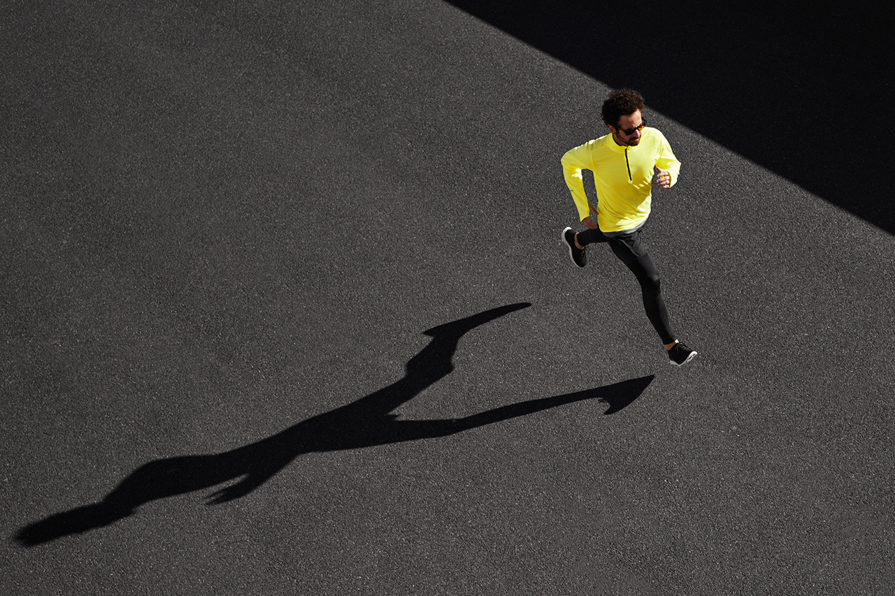 Running man sprinting for success on run. Top view athlete runner training at fast speed at black asphalt. Muscular fit sport model sprinter exercising sprint in yellow sportswear. Caucasian fitness model in his 20s.