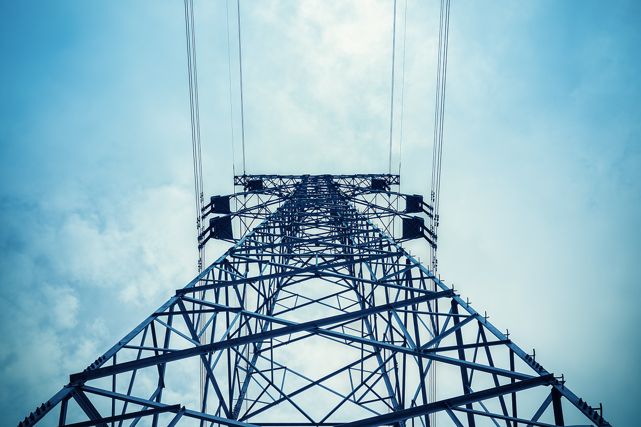 upward view of the power transmission tower in a cloudy sky
