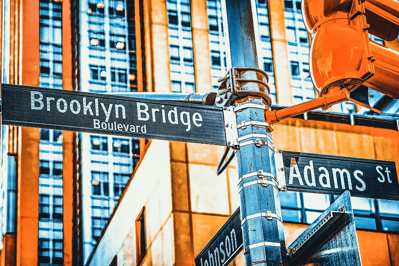New York, USA- September 08, 2017 : Street sign (nameplate) of Brooklyn Bridge and Adams Street and urban cityscape of New York. Midtown district.